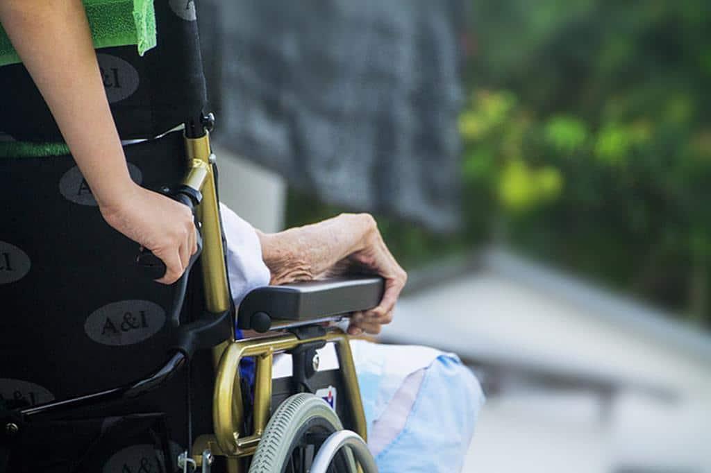 cuidador de idoso empurrando  uma cadeira de rodas