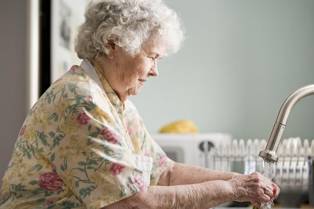 idosa lavando louça sozinha