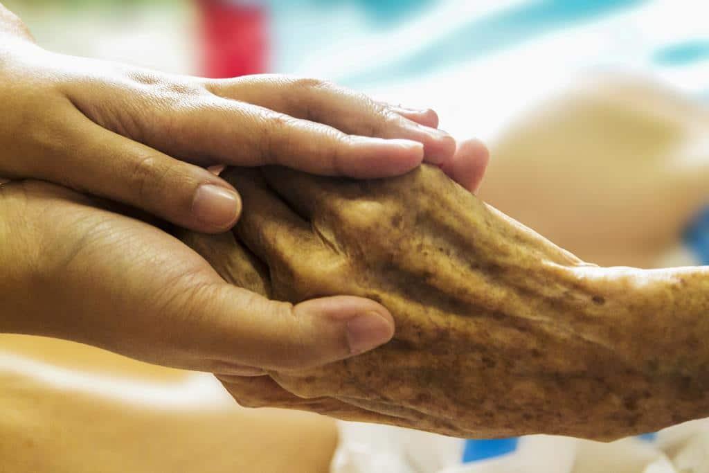 segurando na mão de idoso